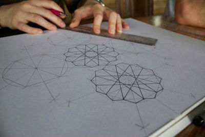 image of a person drawing their own mandala art piece