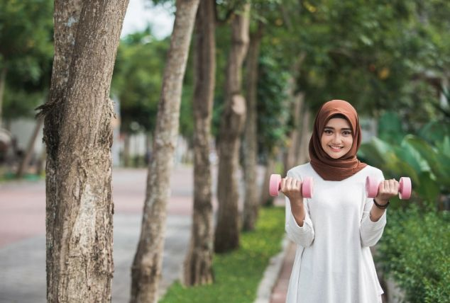 photo of girl with dumbells walking down street for exercise